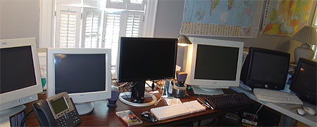 a desk with 6 monitors and a phone
