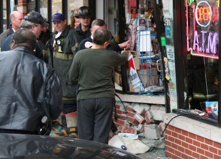 damaged storefront with policeman and firefighters