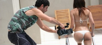 man with camcorder aimed at woman in bikini